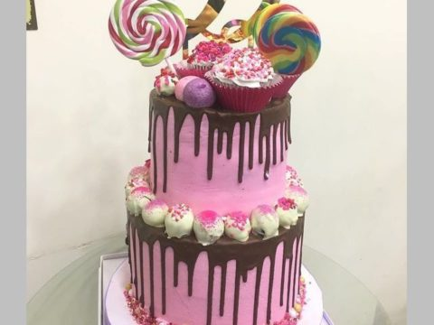 pink chocolate dripping cake with lollipops